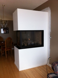 Newly installed peninsula fireplace: primed and ready for painting